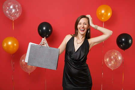 Joyful young girl in black dress putting hand on head, holding packages bags with purchases after shopping on bright red background air balloons. Happy New Year, birthday mockup holiday party concept Stock Photo