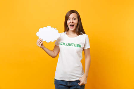 Woman in white t-shirt with written inscription green title volunteer hold empty blank Say cloud speech bubble isolated on yellow background. Voluntary free assistance help charity grace work concept