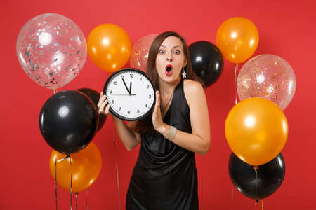 Shocked young woman in black dress celebrating holding round clock on red background air balloon. Time is running out. International Women's Day, Happy New Year, birthday mockup holiday party concept