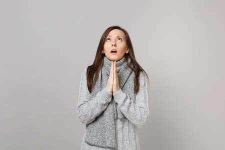 Praying young woman in gray sweater, scarf folded her hands, looking up isolated on grey wall background. Healthy fashion lifestyle, people sincere emotions, cold season concept. Mock up copy space Фото со стока
