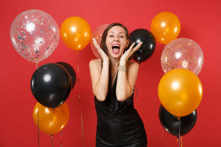 Excited happy young woman in black dress screaming, spreading hands near face on bright red background air balloons. International Women's Day, Happy New Year, birthday mockup holiday party concept Stock Photo
