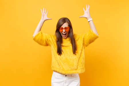 Crazy young woman with closed eyes in fur sweater, heart orange glasses spreading, rising hands up isolated on bright yellow background. People sincere emotions, lifestyle concept. Advertising area