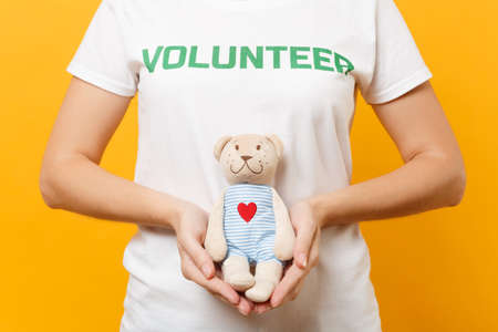 Portrait of woman in white t-shirt with written inscription green title volunteer hold teddy bear plush toy isolated on yellow background. Voluntary free assistance help, charity grace work concept
