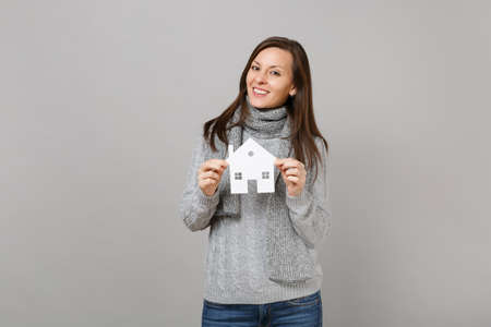 Smiling young woman in gray sweater, scarf holding paper white house isolated on grey background in studio. Healthy fashion lifestyle, people sincere emotions, cold season concept. Mock up copy space 免版税图像