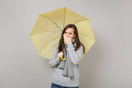 Young woman in gray sweater, scarf covering mouth with hand, sneezing or coughing, hold yellow umbrella isolated on grey background. Healthy lifestyle, ill sick disease treatment, cold season concept
