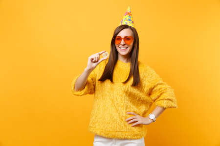 Smiling young woman in orange heart glasses, birthday party hat holding bitcoin, metal coin of golden color, future currency isolated on yellow background. People sincere emotions, lifestyle concept