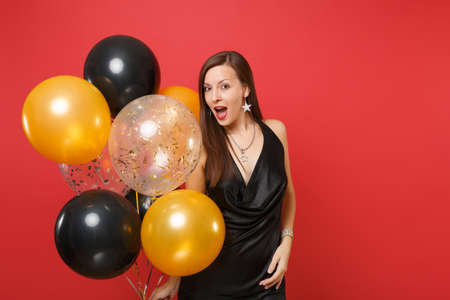 Amazed young woman in little black dress celebrating holding air balloons isolated on red background. St. Valentine's, International Women's Day, Happy New Year, birthday mockup holiday party concept 免版税图像