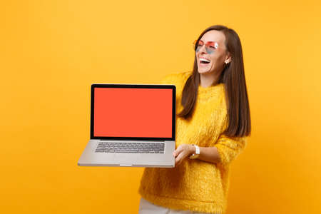 Laughing young woman in heart eyeglasses holding laptop pc computer with blank black empty screen isolated on bright yellow background. People sincere emotions, lifestyle concept. Advertising area Фото со стока