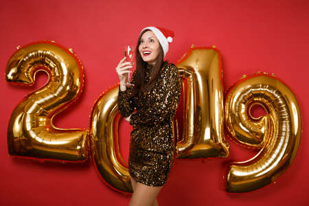 Merry Santa girl in shiny glitter dress, Christmas hat hold champagne isolated on bright red wall background, golden numbers air balloons studio portrait. Happy New Year 2019 holiday party concept Banco de Imagens
