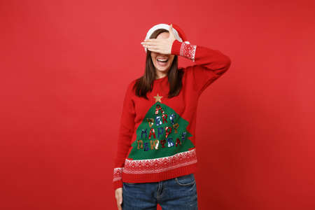 Smiling young Santa girl in knitted sweater, Christmas hat covering eyes with hand isolated on bright red wall background. Happy New Year 2019 celebration holiday party concept. Mock up copy space