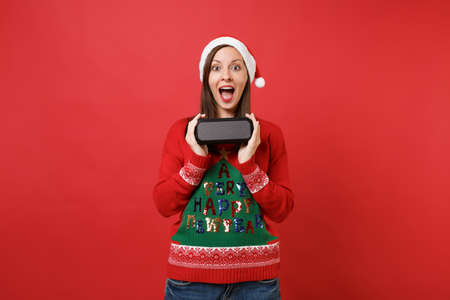 Surprised young Santa girl keeping mouth wide open hold portable wireless bluetooth music speaker isolated on red background. Happy New Year 2019 celebration holiday party concept. Mock up copy space Stock Photo