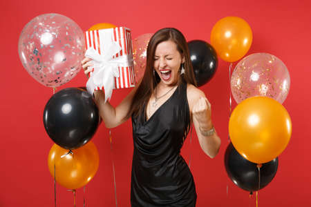 Crazy woman in black dress celebrating screaming, holding red box with gift, present, clenching fist like winner on red background air balloons. Happy New Year, birthday mockup holiday party concept