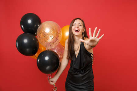 Laughing cheerful young woman in black dress pointing hand on camera and holding air balloons, celebrating isolated on red background. Women's Day Happy New Year birthday mockup holiday party concept Banco de Imagens