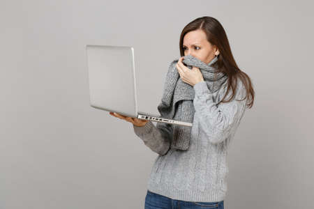 Displeased young woman in gray sweater covering mouth with scarf, working on laptop pc computer isolated on grey wall background. Healthy lifestyle, online treatment consulting, cold season concept