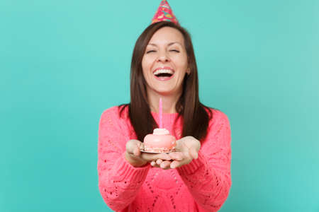 Laughing young woman in knitted pink sweater and birthday hat holding in hand cake with candle isolated on blue turquoise wall background studio portrait. People lifestyle concept. Mock up copy space Stock Photo