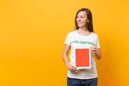 Mujer en camiseta blanca inscripción escrita título verde voluntario mantenga tablet pc, pantalla vacía en blanco aislada sobre fondo amarillo. Ayuda de asistencia gratuita voluntaria, concepto de trabajo de gracia de caridad