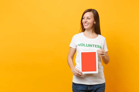 Woman in white t-shirt written inscription green title volunteer hold tablet pc computer, blank empty screen isolated on yellow background. Voluntary free assistance help, charity grace work concept Stock fotó