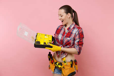 Strong young handyman woman in plaid shirt, denim shorts, kit tools belt full of different instruments holding toolbox isolated on pink background. Female in male work. Renovation occupation concept Standard-Bild - 112302395