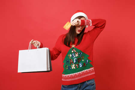Santa girl covering eyes with hand hold credit card, packages bags with purchases after shopping isolated on red background. Happy New Year 2019 celebration holiday party concept. Mock up copy space Stock Photo