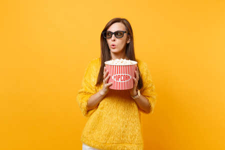 Suspicious puzzled young girl in 3d imax glasses watching movie film looking aside holding bucket of popcorn isolated on bright yellow background. People sincere emotions in cinema, lifestyle concept 免版税图像