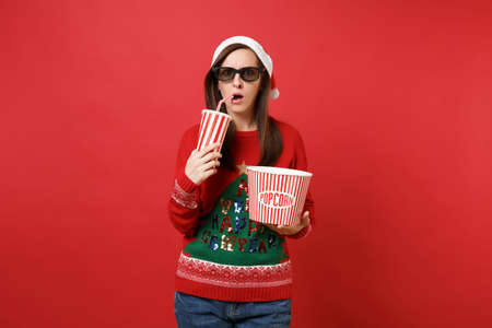 Shocked young Santa girl in 3d glasses watching movie film holding popcorn, cup of soda isolated on red wall background. Happy New Year 2019 celebration holiday party concept. Mock up copy space