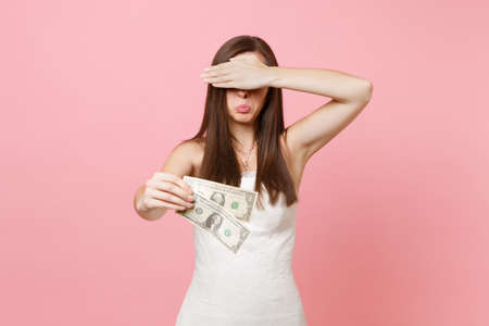 Offended bride woman in white wedding dress covering eyes with palm holding one dollar bills isolated on pastel pink background. Lack of money. Organization of wedding celebration concept. Copy space