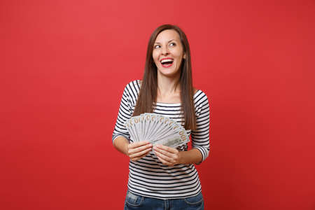 Smiling young woman in striped clothes dreaming, looking up, holding bundle lots of dollars, cash money isolated on red wall background. People sincere emotions, lifestyle concept. Mock up copy space