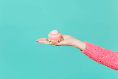 Close up female hold in hand pink cake isolated on blue turquoise wall background. Proper nutrition or sweets dessert fast food dieting morning concept. Copy space for advertisement. Advertising area 스톡 콘텐츠