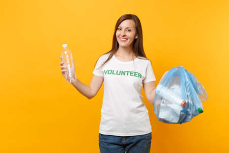 Woman in t-shirt volunteer, trash bag isolated on yellow background. Voluntary free assistance help, charity grace. Environmental pollution problem. Stop nature garbage environment protection concept Stock fotó