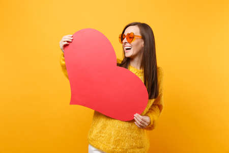 Laughing pretty young woman in fur sweater and orange heart eyeglasses holding empty blank red heart isolated on bright yellow background. People sincere emotions, lifestyle concept. Advertising area 免版税图像