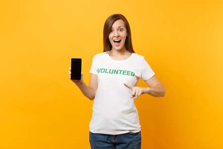 Woman in white t-shirt written inscription green title volunteer hold mobile phone with blank empty screen isolated on yellow background. Voluntary free assistance help, charity grace work concept Stock Photo