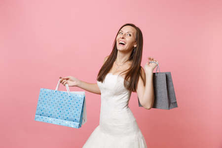 Portrait of cheerful bride woman in wedding dress looking up holding multi colored packages bags with purchases after shopping isolated on pink background. Organization of wedding concept. Copy space Stockfoto