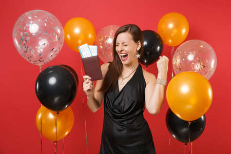 Happy young girl in black dress celebrating, holding passport, boarding pass tickets, doing winner gesture on bright red background air balloons. Happy New Year, birthday mockup holiday party concept Archivio Fotografico