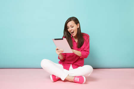 Full length portrait woman in rose shirt blouse, white pants sitting on floor hold tablet pc isolated on pink blue pastel wall background studio. Fashion lifestyle concept. Mock up copy space. 写真素材