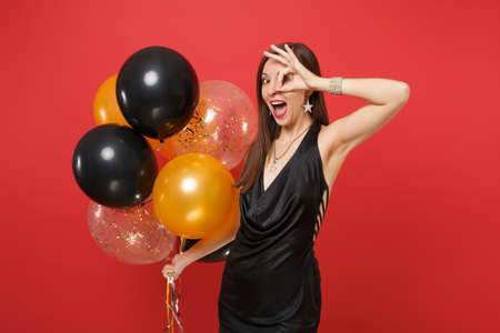 Funny young woman in black dress celebrating showing OK sign near eyes holding air balloons isolated on red background. International Women's Day Happy New Year, birthday mockup holiday party concept