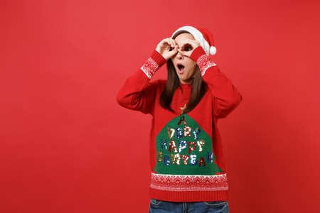 Surprised Santa girl keeping mouth open, holding hands near eyes, imitating glasses or binoculars isolated on red background. Happy New Year 2019 celebration holiday party concept. Mock up copy space