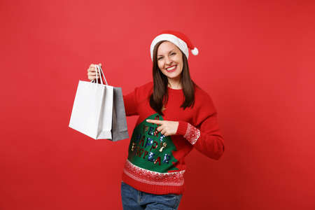 Smiling young Santa girl pointing index finger on packages bags with purchases after shopping isolated on red background. Happy New Year 2019 celebration holiday party concept. Mock up copy space