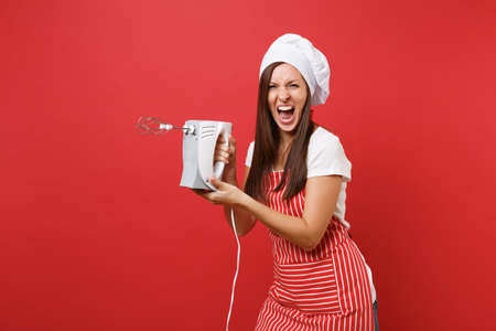Housewife female chef cook or baker in striped apron white t-shirt toque chefs hat isolated on red wall background. Woman hold kitchen mixer, cook Christmas ginger biscuit. Mock up copy space concept