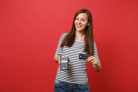 Pretty woman holding wireless modern bank payment terminal to process and acquire credit card payments, black card isolated on red background. People sincere emotions, lifestyle. Mock up copy space Фото со стока