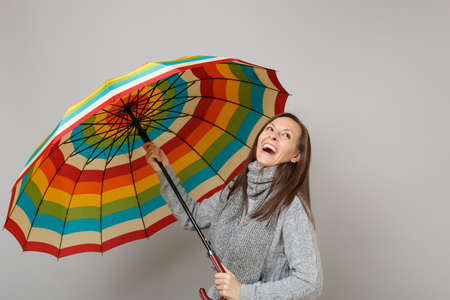 Laughing young woman in gray sweater, scarf holding colorful umbrella isolated on grey background in studio. Healthy fashion lifestyle people sincere emotions, cold season concept. Mock up copy space