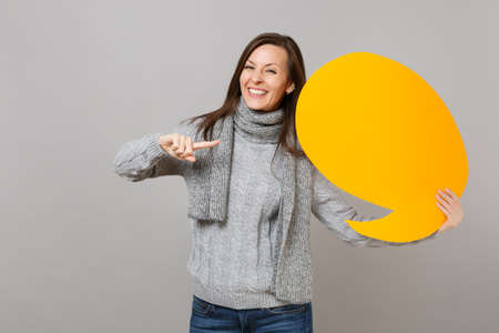 Pretty woman in sweater, scarf point index finger on yellow empty blank Say cloud, speech bubble isolated on grey background. Healthy fashion lifestyle, people sincere emotions, cold season concept 스톡 콘텐츠