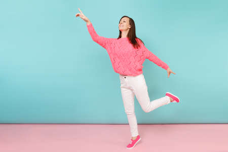 Full length portrait of smiling young woman in knitted rose sweater, white pants posing isolated on bright pink blue pastel wall background in studio. Fashion lifestyle concept. Mock up copy space Stock Photo
