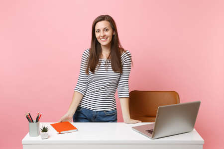 Young smiling woman in casual clothes work, standing near white desk with contemporary pc laptop isolated on pastel pink background. Achievement business career concept. Copy space for advertisement