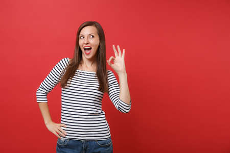 Portrait of cheerful excited young woman in casual striped clothes looking up, showing OK sign isolated on bright red wall background. People sincere emotions, lifestyle concept. Mock up copy space