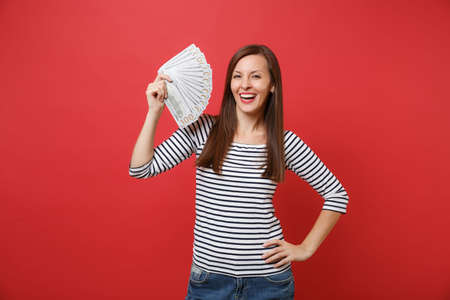 Portrait of smiling young woman in striped clothes holding bundle lots of dollars, cash money isolated on bright red wall background. People sincere emotions, lifestyle concept. Mock up copy space