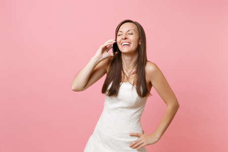 Laughing bride woman in white wedding dress talking on mobile phone, conducting pleasant conversation isolated on pastel pink background. Wedding to do list. Organization of celebration. Copy space