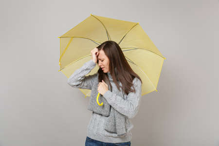 Crying young woman in gray sweater, scarf putting hand on head, holding yellow umbrella isolated on grey background. Healthy fashion lifestyle, people emotions cold season concept. Mock up copy space