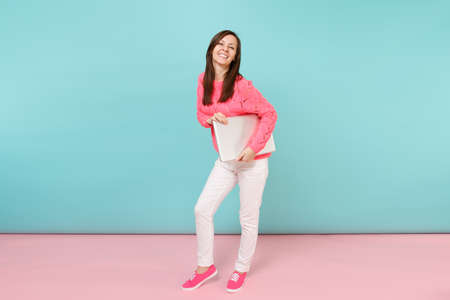 Full length portrait of woman in knitted rose sweater white pants holding laptop pc computer isolated on bright pink blue pastel wall background in studio Fashion lifestyle concept Mock up copy space