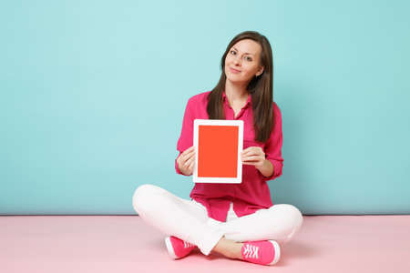 Full length portrait woman in rose shirt blouse, white pants sitting on floor hold tablet pc isolated on bright pink blue pastel wall background studio. Fashion lifestyle concept. Mock up copy space