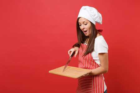 Housewife female chef cook or baker in striped apron, white t-shirt, toque chefs hat isolated on red wall background. Housekeeper woman holding wooden cutting board, knife. Mock up copy space concept